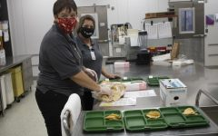 The lunch ladies prepare the chips and salsa for lunch on Sept. 23.