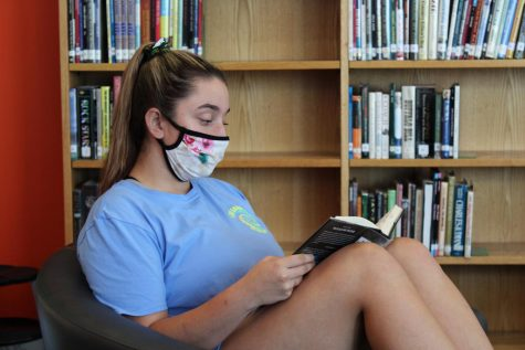 Senior Maddie Turner reads in the library.