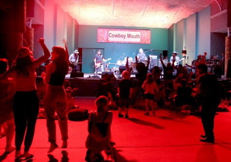 Cowboy Mouth plays for audience under red lights at the main stage.