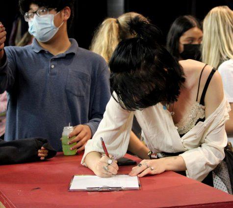 Aubrey Powell signs in.